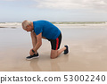 Senior man tying shoe laces at the beach 53002240
