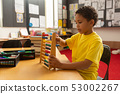 schoolboy learning mathematics with abacus in a classroom  53002267