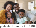 Happy African American family sitting on sofa and looking at 53002304