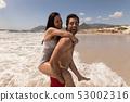 Man giving woman piggyback ride and having fun at beach 53002316