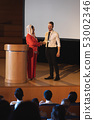 Business colleague standing and discussing with each other in front of the audience in auditorium 53002346