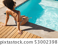 Young mixed-race woman sitting at poolside in backyard of home 53002398