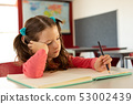 Girl writing on notebook in a classroom 53002439