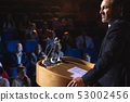 Businessman standing on a stage of auditorium for presentation 53002456