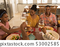 Multi-generation family toasting glasses of wine on dining table 53002585