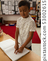 Blind schoolboy reading a braille book in classroom 53002615