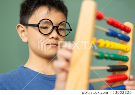 Boy learning math with abacus against green chalkboard in a classroom 53002820