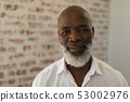 Black senior man smiling and standing at home 53002976