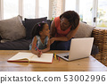 Grandmother helping her granddaughter with homework in living room 53002996