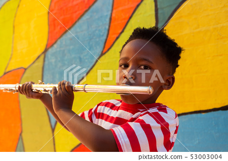 Schoolboy playing flute instrument in the school playground 53003004