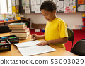 Schoolboy studying at desk in a classroom 53003029