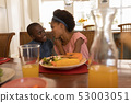 Siblings interacting with each other on dining table 53003051