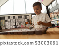 Schoolboy playing xylophone in a classroom 53003091