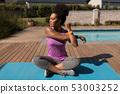 Woman performing stretching exercise in the backyard of home 53003252