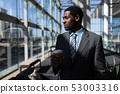 African-American of businessman with coffee cup looking away in office 53003316