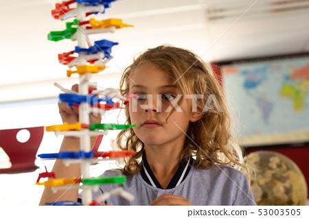 Schoolgirl learning on science model in classroom 53003505