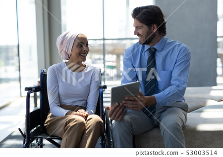 Happy disabled mixed-race female executive with Caucasian businessman discussing over digital tablet 53003514