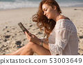 Young Caucasian woman using digital tablet on the beach 53003649