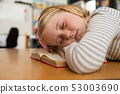 Schoolgirl sleeping on book at desk in the classroom 53003690