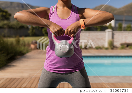 Woman exercising with kettlebell in the backyard of home 53003755