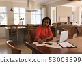 Woman calculating invoices at home 53003899