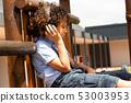 Schoolgirl listening music on headphones in the school playground 53003953