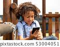 Schoolgirl using mobile phone in the school playground 53004051