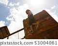 Schoolgirl climbing a wall in the school playground 53004061