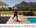 Senior woman performing stretching exercise in the backyard of home 53004182