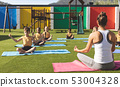 Trainer teaching yoga to students in school playground 53004328