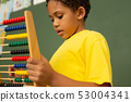 Schoolboy learning mathematics with abacus in a classroom 53004341