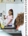 Mixed-race ethnicity schoolgirl analyzing DNA structure model at school 53004359