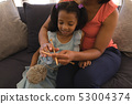 Grandmother teaching her granddaughter how to knitt in living room 53004374
