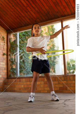 Schoolgirl spinning a hula hoop around her waist 53004403