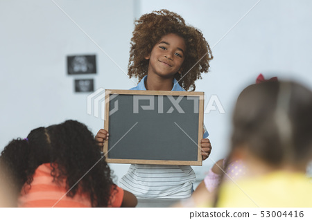 African ethnicity schoolboy holding a slate and looking at camera in classroom 53004416