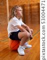 Schoolgirl sitting on a basketball in basketball court 53004471