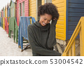 Young African American woman with hand in hair standing at beach hut 53004542