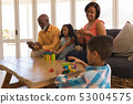 Multi-generation family enjoying their free time in living room 53004575