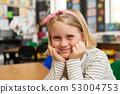 Schoolgirl sitting at desk in the classroom at school 53004753
