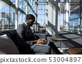 African-American businessman sitting on the sofa and using laptop in modern office 53004897