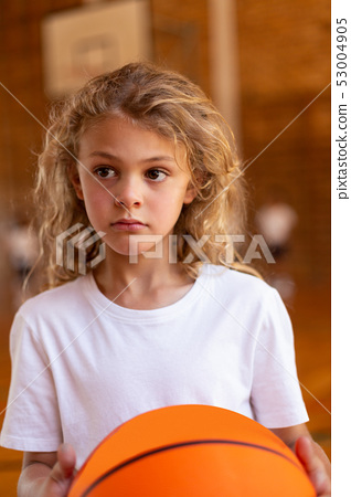 Schoolgirl with a basketball standing in basketball court 53004905