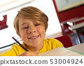 Happy boy looking at camera while drawing sketch on book at desk in a classroom 53004924