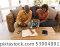 Grandfather and grandmother helping his grandson with homework in living room 53004991