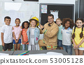 Happy students standing with firefighter in classroom 53005128