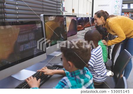 Teacher teaching student in computer room 53005145