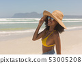 Young African American woman in yellow bikini, hat and sunglasses standing on the beach 53005208
