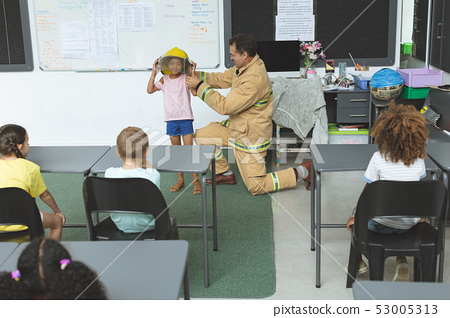 Firefighter kneeling while he is teaching to a schoolgirl about fire safety  53005313