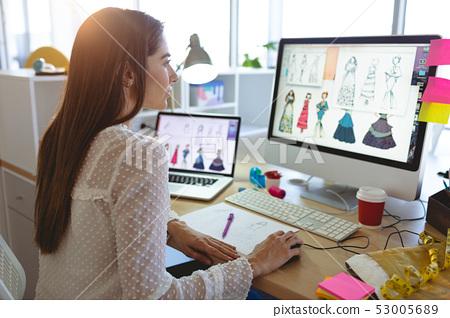 Female fashion designer working on computer at desk  53005689