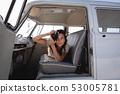 Beautiful woman capturing photo with digital camera in camper van  53005781