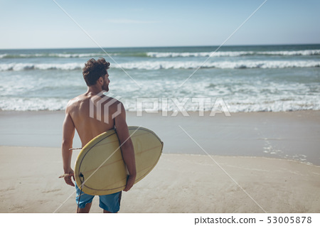 Male surfer with a surfboard standing on a beach 53005878
